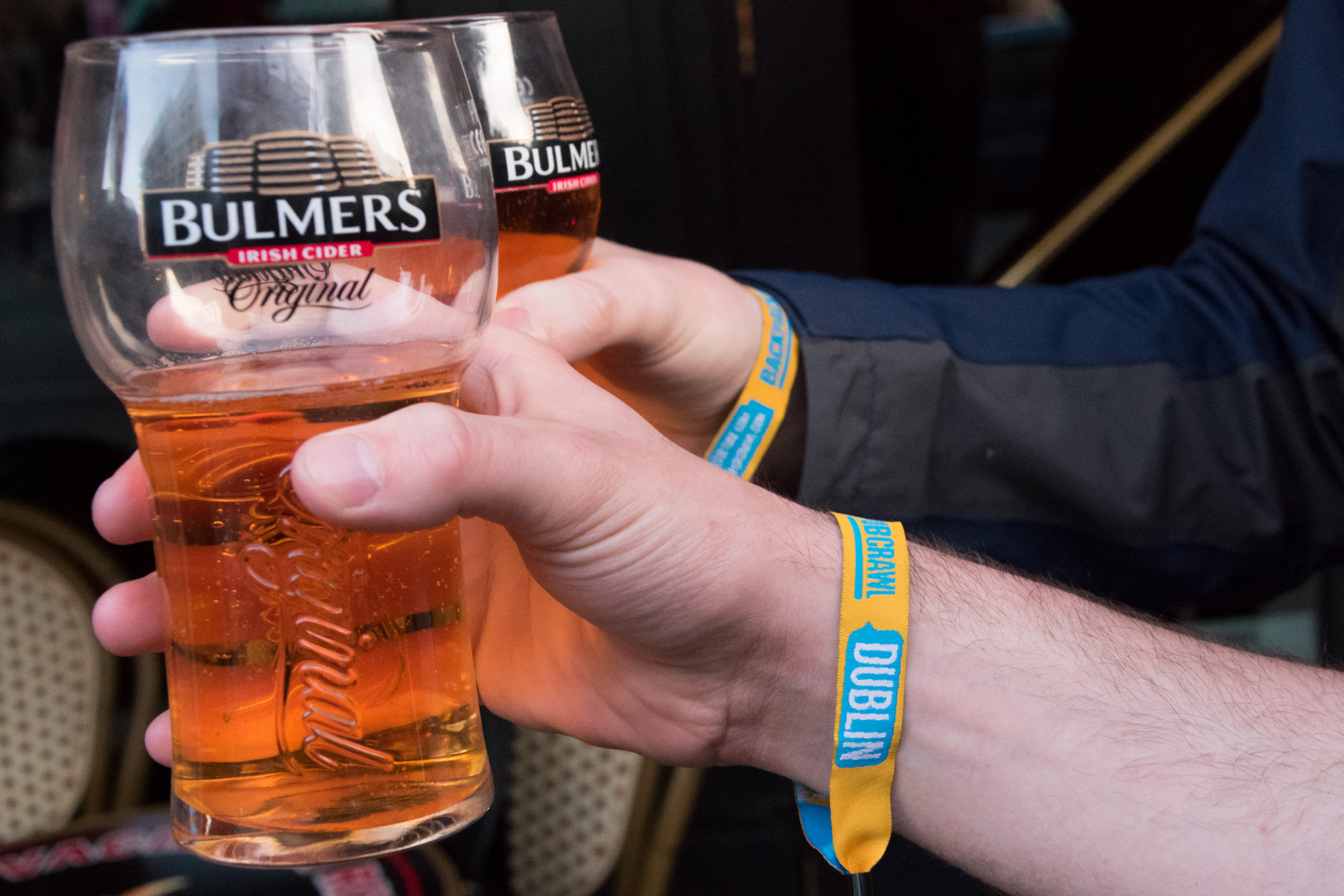 Two hands holding glasses of beer and displaying Dublin pub crawl wristbands during a bar crawl in Dublin city, Ireland