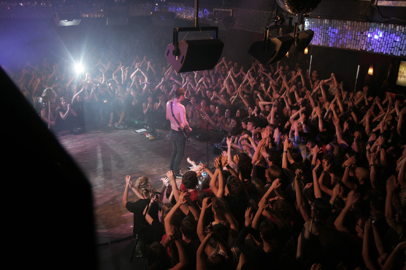 A singer on stage at Lucerna Music bar & venue in Prague at night surrounded by cheering fans