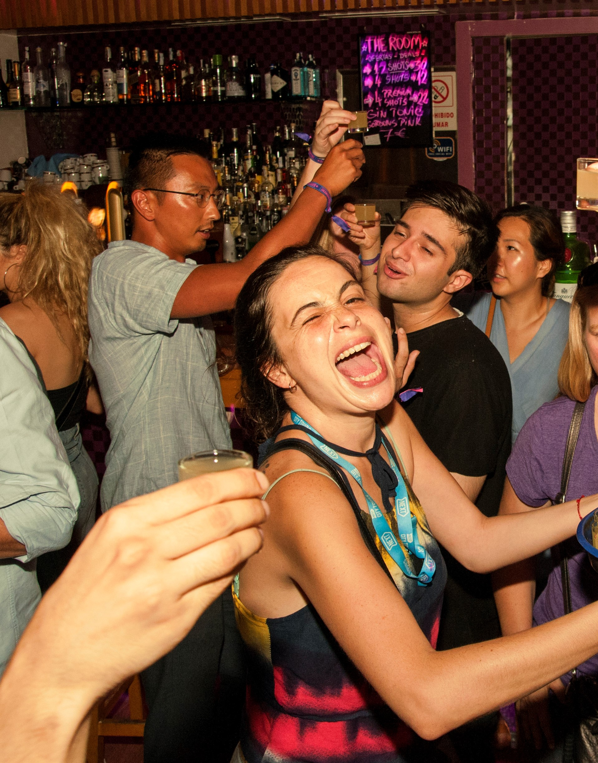 A Barcelona pub crawl guide in the middle of a group of people having shots during a bar crawl in Barcelona