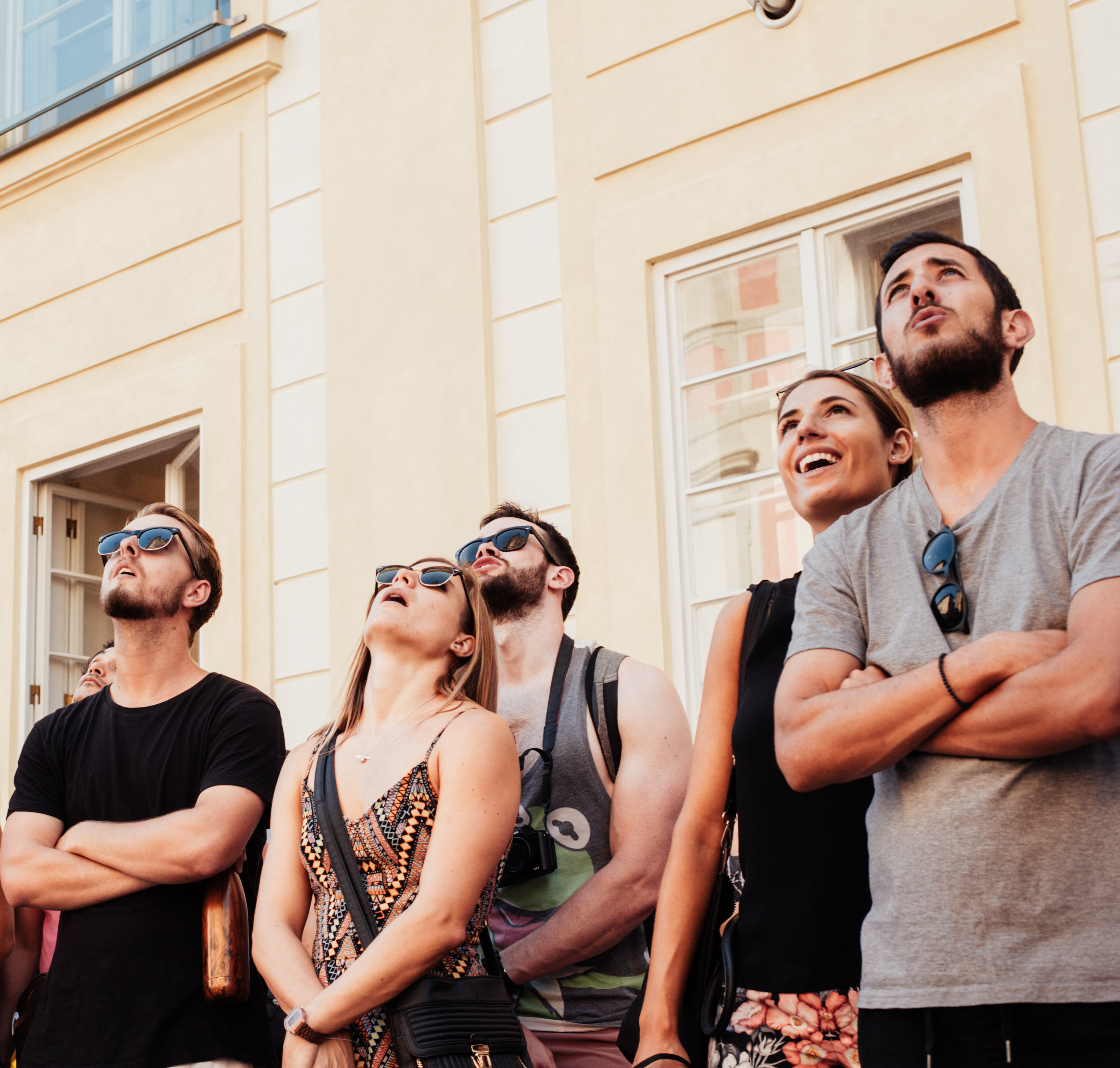 Tourists looking up at a building on a free tour in Prague