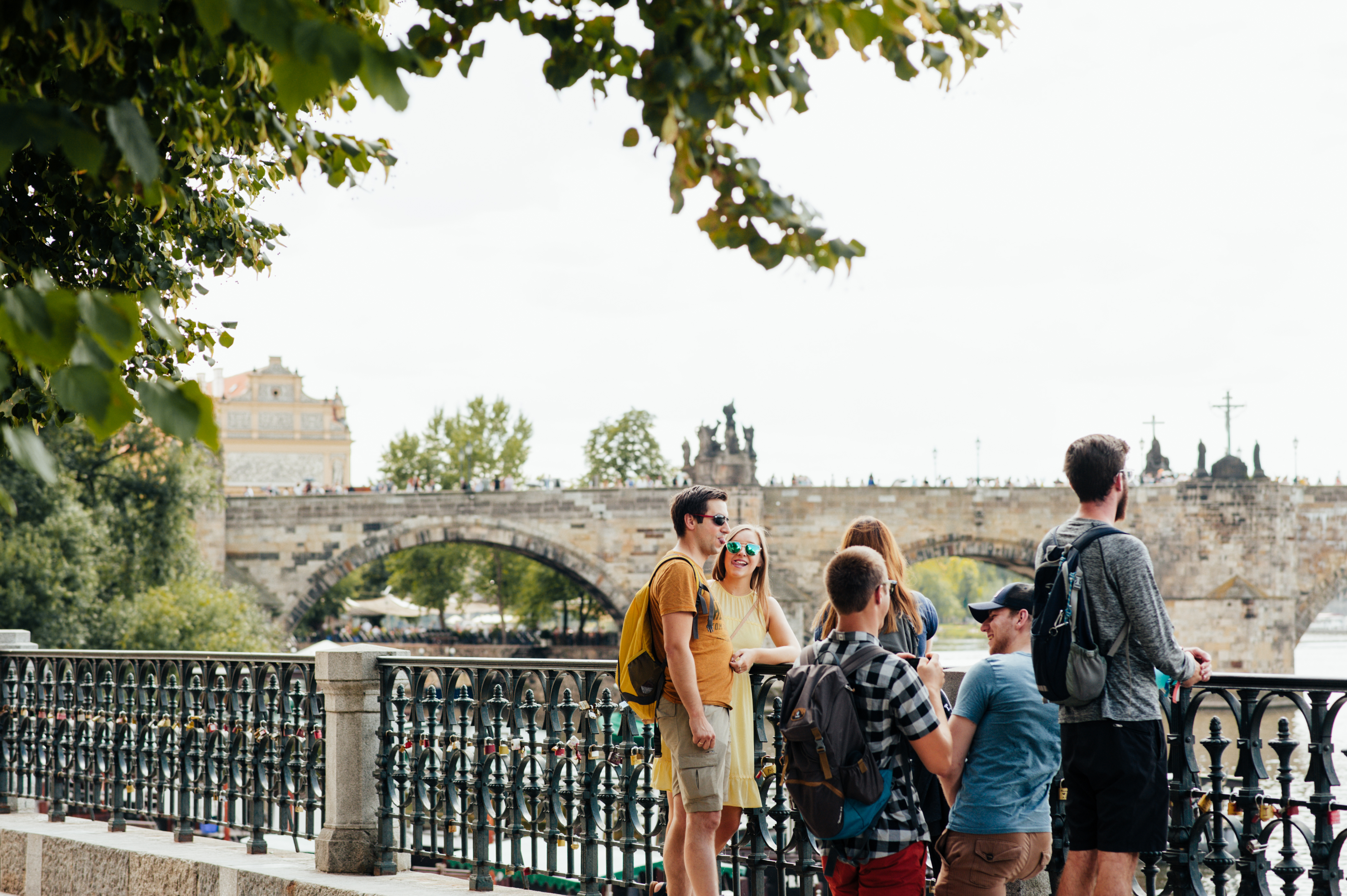 some tourists in prague during a free walking tour, with Charles Bridge in the distance