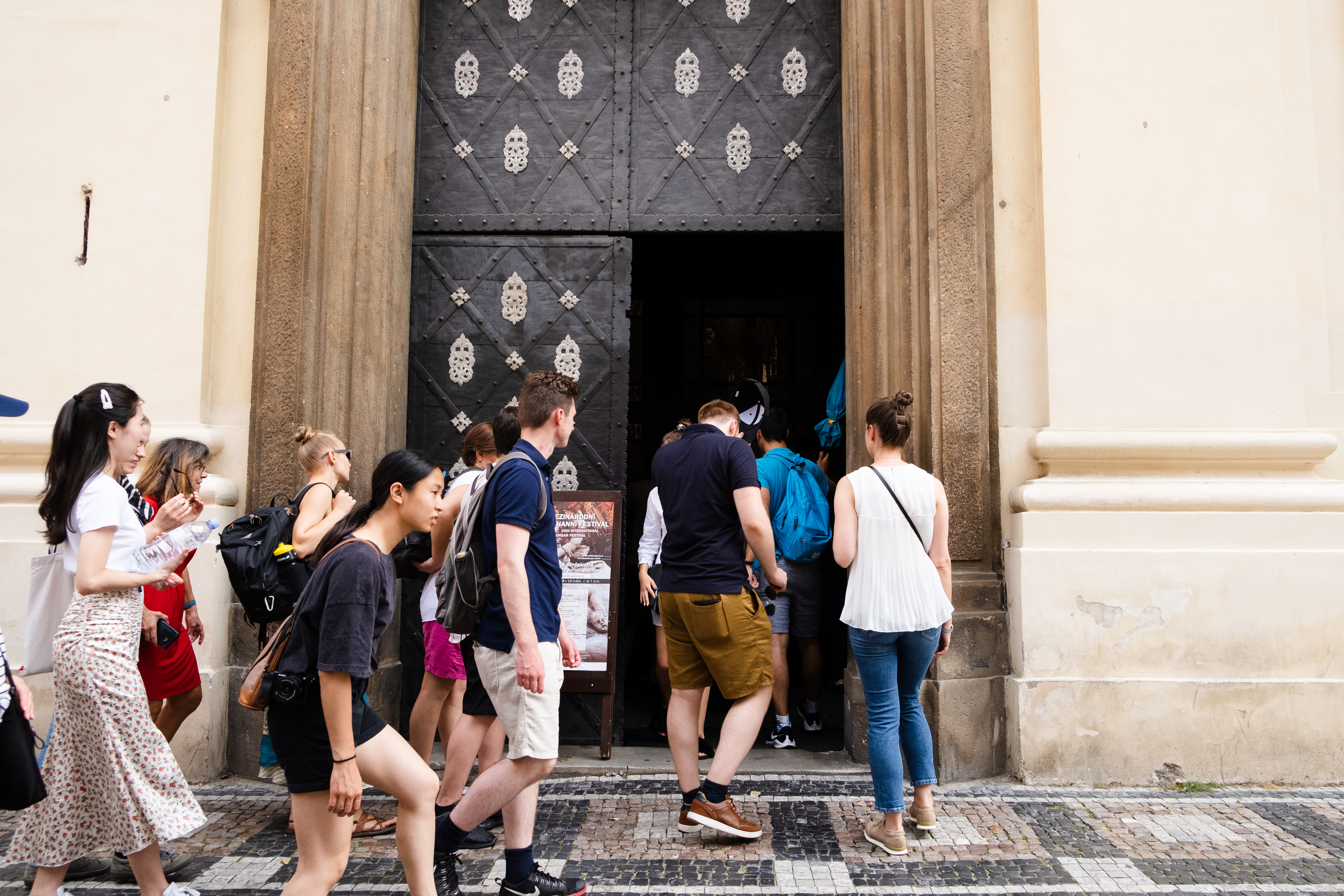 A group of tourists entering a cathedral during a free walking tour of Prague