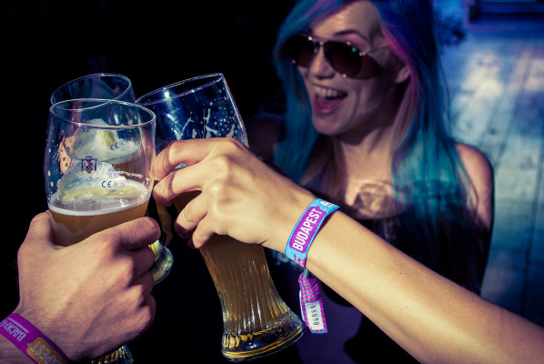 Backpacker Pub Crawl Budapest wristband on wrist of customer holding glass of beer