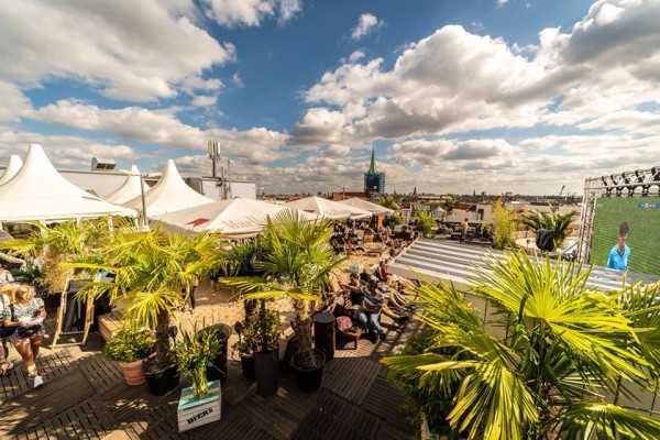 Elevated view of Deck % rooftop bar in Berlin at daytime, with people relaxing and drinking surrounded by palm trees