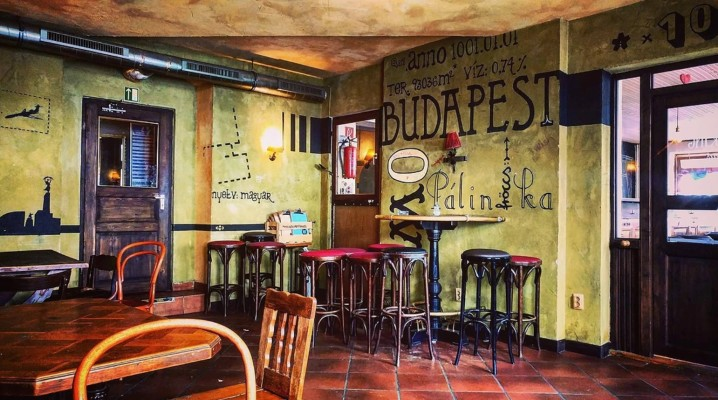 The interior of Szimpla bar in Berlin - ruin pub style, mismatched furniture, red tiled floor and writing on the wall