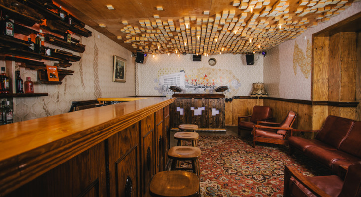 The interior of pomegradeneck bar in Berlin, retro style decor with dark wood furnishings and bar stools