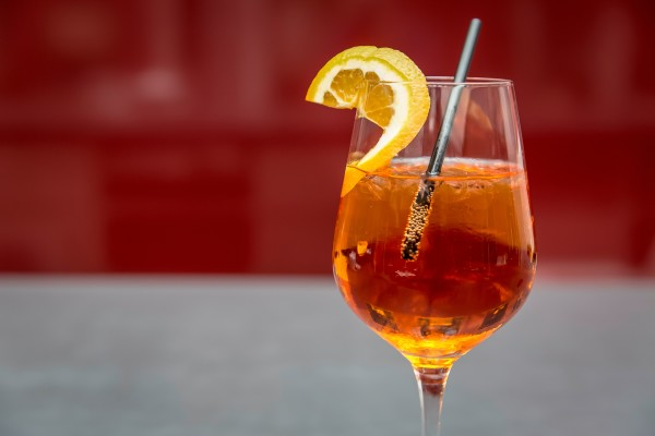aperol cocktail with straw and slice of lemon on rim of glass